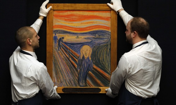 """File photo shows Sotheby's employees posing for a photograph with Edvard Munch's painting """"The scream"""" at Sotheby's auction house in London"""